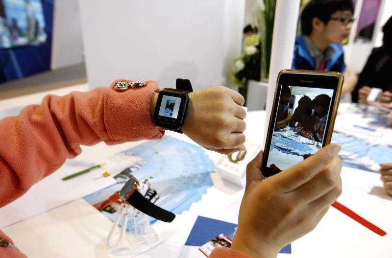 A staff member shows an electronic product, which can be connected with mobile phones with bluetooth technology, during the 2nd China (Shanghai) International ...