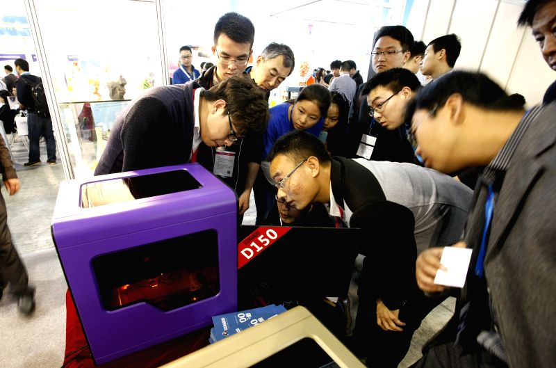Visitors view a 3D printer during the 2nd China (Shanghai) International Technology Fair in Shanghai, east China, April 24, 2014. The fair kicked off here ...
