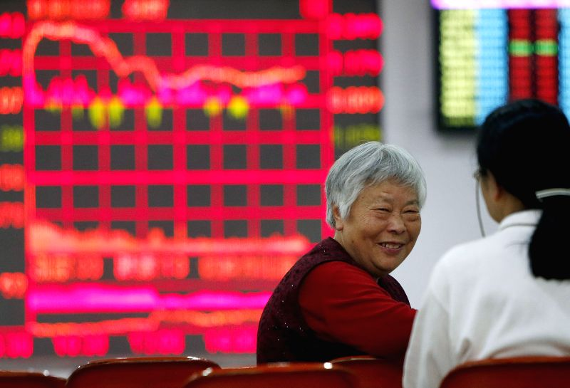 Investors focus on stock market at a business hall in Shanghai, east China, April 27, 2015.  The benchmark Shanghai Composite Index went up 3.04 percent, or ...