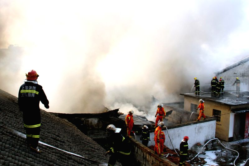 Firemen spray water to douse a fire that engulfed a factory in the Jinshan District in Shanghai, east China, Dec. 29, 2014. No casualties were reported after the ..