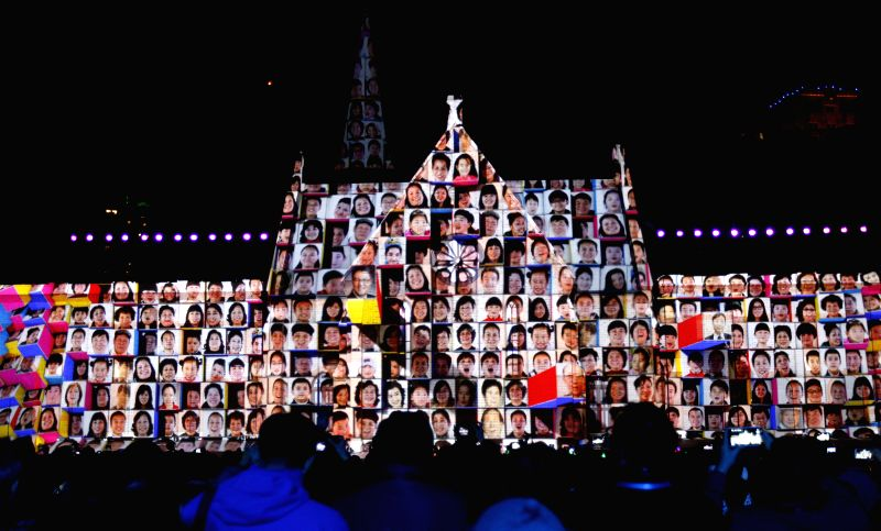 Citizens watch an illuminated portrait photo display during a light show marking the coming of the New Year's Day of 2015 in east China's Shanghai, Dec. 31, 2014. ..
