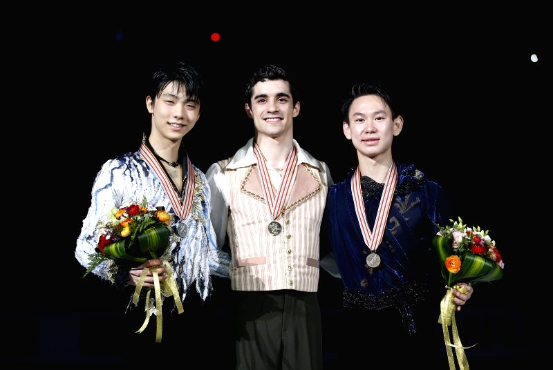Gold medalist Javier Fernandez (C) of Spain, silver medalist Yuzuru Hanyu (L) of Japan and bronze medalist Denis Ten of Kazakhstan pose during the awarding ...