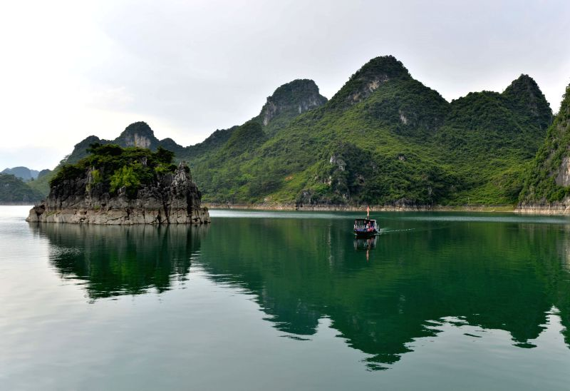 A sightseeing cruise travels on Dalong Lake scenic spot in Shanglin County, south China's Guangxi Zhuang Autonomous Region, July 3, 2014. The Dalong Lake scenic ...