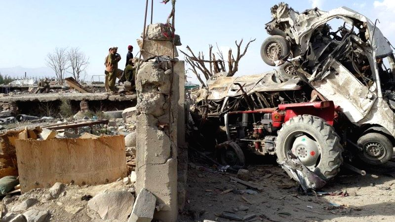 People gather beside destroyed vehicles after a suicide car bomb in Urgun district of Paktika province, Afghanistan, July 15, 2014. At least 30 people were killed ...