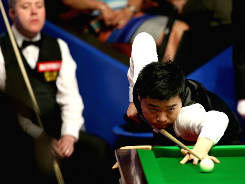 China's Ding Junhui competes during the third session of the second round match against Scotland's John Higgins at the 2015 World Snooker Championship at the ...