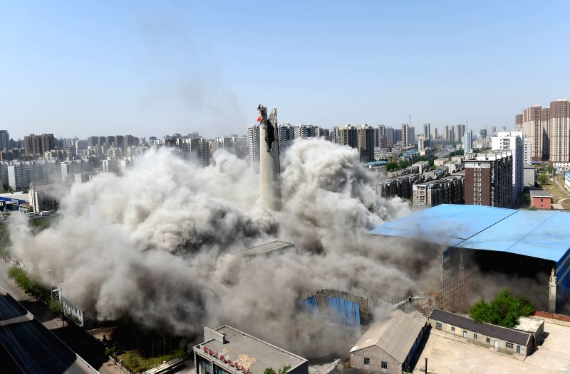 Photo taken on April 28, 2014 shows a 150-meter-high chimney of Shenyang No.3 Power Plant being demolished by blasting in Shenyang, capital of northeast China's ..