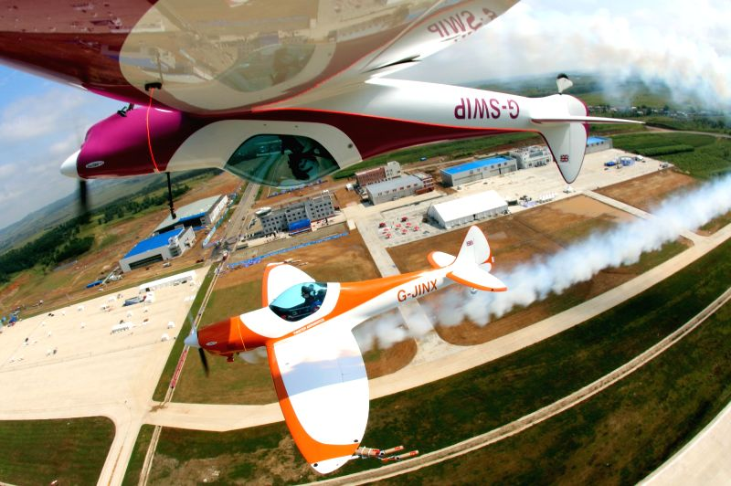 Members of the Twister aerobatics team do a stunt during a test flight for upcoming performances during the 2014 Shenyang Faku International Flight Convention, an .