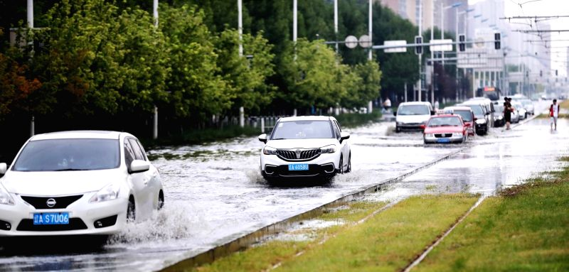 SHENYANG, Aug. 7, 2018 - Vehicles wade through a flooded street in Shenyang, capital of northeast China's Liaoning Province, Aug. 7, 2018. A heavy rainfall caused the flood in Shenyang on Tuesday.