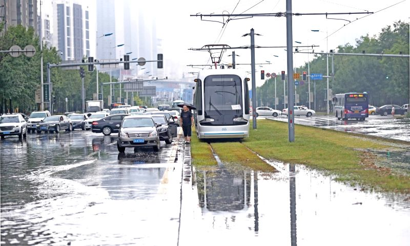 SHENYANG, Aug. 7, 2018 - Vehicles wait to go through a flooded street in Shenyang, capital of northeast China's Liaoning Province, Aug. 7, 2018. A heavy rainfall caused the flood in Shenyang on ...