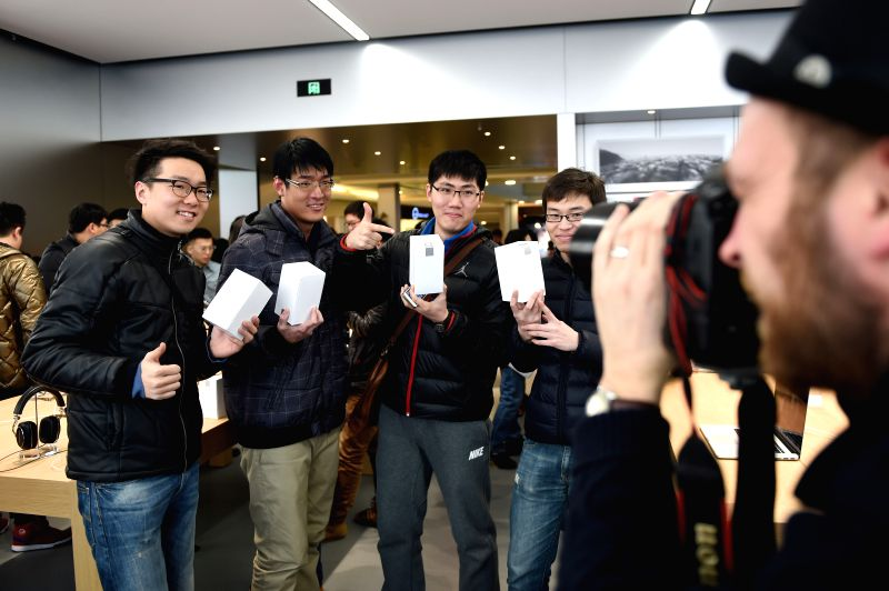 Customers pose for photos in the Apple retail store in Shenyang, capital of northeast China's Liaoning Province, Feb. 28, 2015. The first Apple retail store in ...