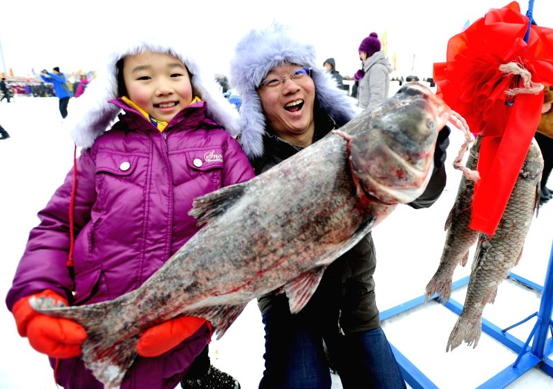 Tourists pose for a photo with a big fish during the 3rd winter fishing festival in Wolong Lake, Kangping of northeast China's Liaoning Province, Jan. 18, 2015. ...