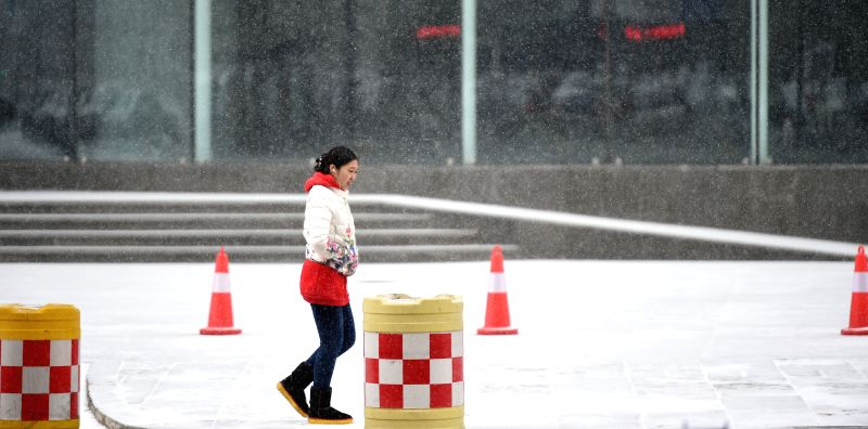 A woman walks in snow in Shenyang, capital of northeast China's Liaoning Province, Jan. 5, 2015. The city's meteorological station issued a blue alert for cold wave