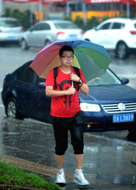SHENYANG, July 21, 2016 - A man walks in rain in Shenyang, capital of northeast China's Liaoning Province, July 21, 2016. Shenyang's meteorological bureau issued an orange alert for rainstorm on ...