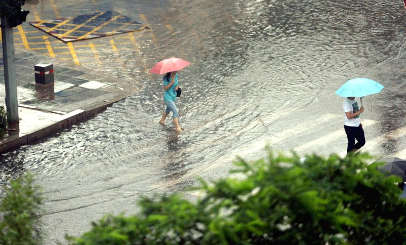 SHENYANG, July 21, 2016 - People walk on a flooded road in Shenyang, capital of northeast China's Liaoning Province, July 21, 2016. Shenyang's meteorological bureau issued an orange alert for ...