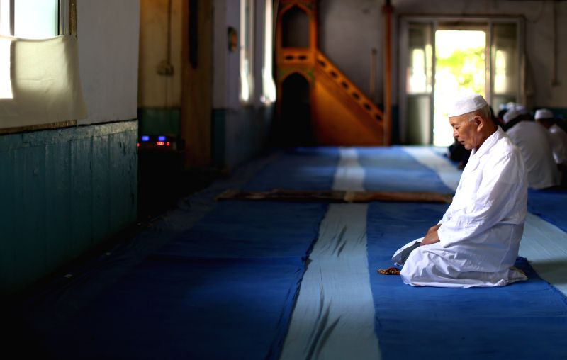 A muslim prays in a mosque in Shenyang, capital of northeast China's Liaoning Province, July 29, 2014. Muslims in Shenyang celebrated Eid al-Fitr on Tuesday, ...