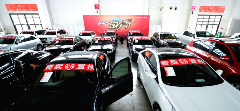 A visitor selects secondhand motorcars during the 2014 China (Shenyang) Auto Fair Expo in Shenyang, capital of northeast China's Liaoning Province, May 7, 2014. The .