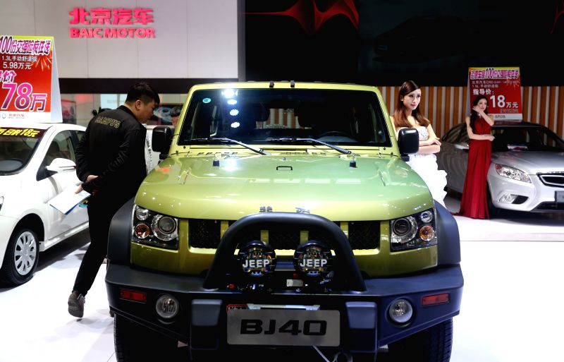 A visitor watches a BJ40 jeep during the 2014 China (Shenyang) Auto Fair Expo in Shenyang, capital of northeast China's Liaoning Province, May 7, 2014. The expo, ...