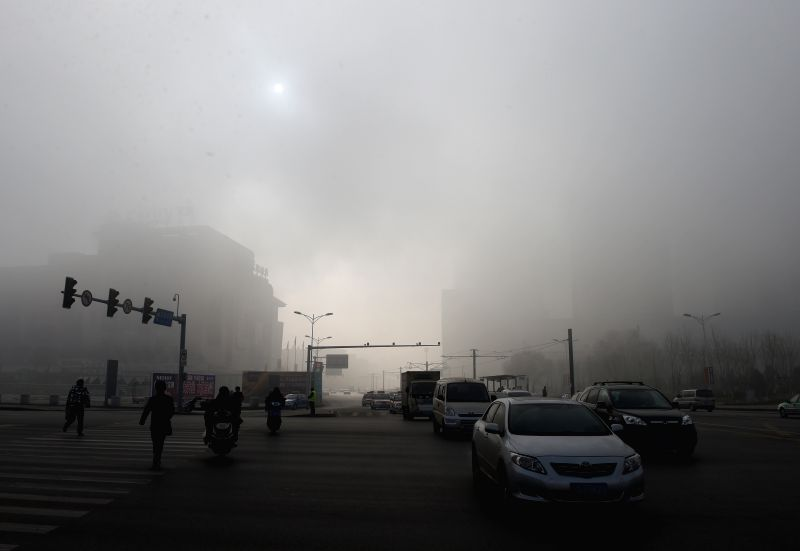 People and vehicles move in smog in Shenyang, capital of northeast China's Liaoning Province, Nov. 21, 2014.