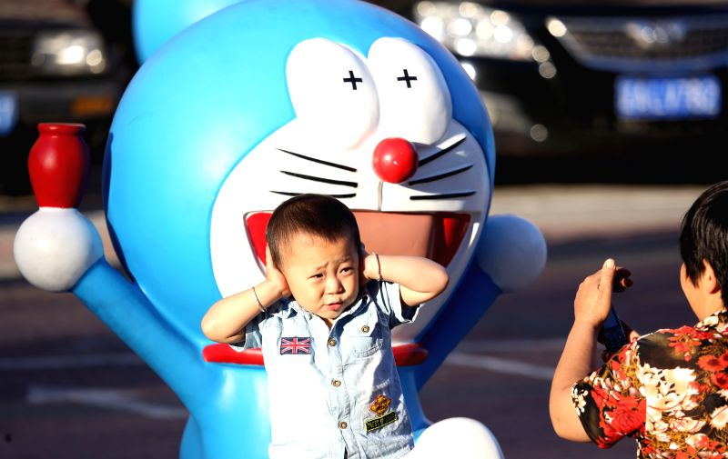 A boy poses for a photo with a Doraemon model in Shenyang, capital of northeast China's Liaoning Province, Sept. 4, 2014. A total of 50 Doraemon models were ...