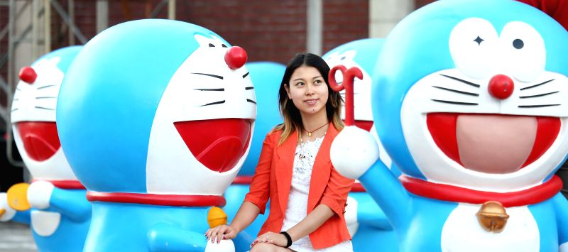 A citizen poses for photo with Doraemon models in Shenyang, capital of northeast China's Liaoning Province, Sept. 4, 2014. A total of 50 Doraemon models were ...