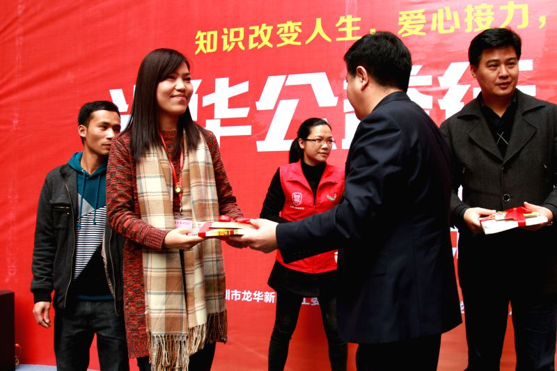 A representative receives donated books at a book donation ceremony in Shenzhen, south China's Guangdong Province,  Feb. 4, 2015. China Guanghua Foundation donated .