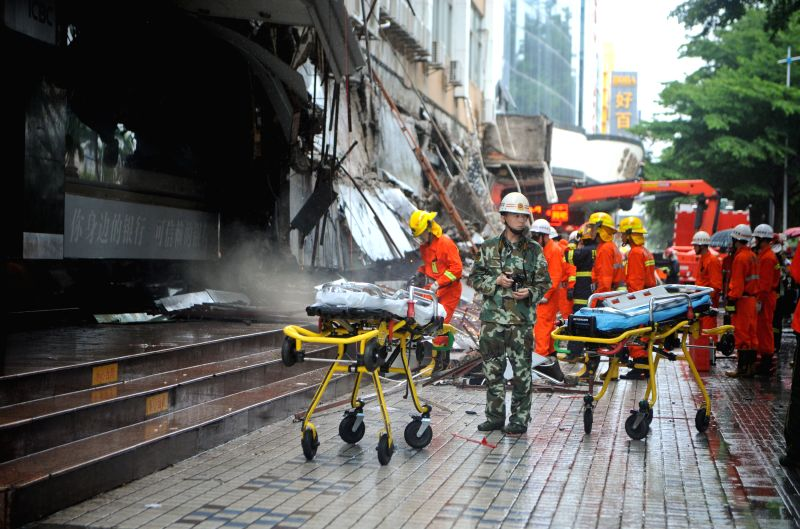 Rescuers work at the site where an overhang above a building's first floor collapsed in Shenzhen, south China's Guangdong Province, July 18, 2014. Three people ...