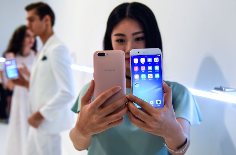 SHENZHEN, June 9, 2017 - A model presents newly-release OPPO smartphone R11 at a press conference in Shenzhen, south China's Guangdong Province, June 9, 2017. The new smartphone is featured with ...