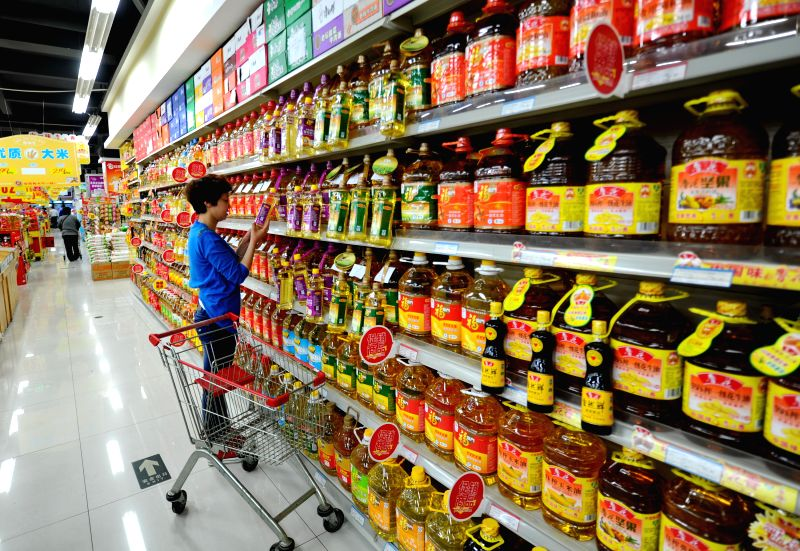 A woman goes shopping at a supermarket in Shijiazhuang, capital of north China's Hebei Province, April 9, 2014. China's consumer price index (CPI), a main ...