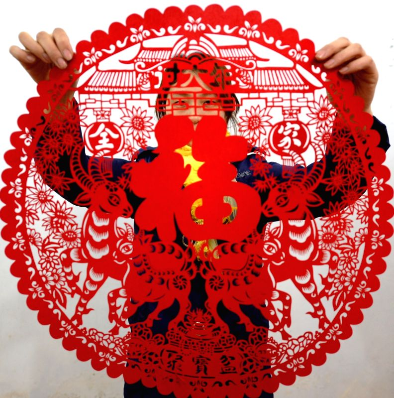 The inheritor of Jizhou paper-cutting Kang Xiaoyan demonstrates her paper-cut work which celebrates the upcoming Chinese Year of Goat in Shijiazhuang, capital ..