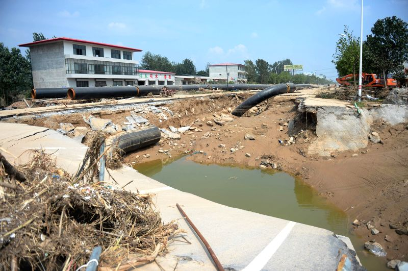 SHIJIAZHUANG, July 24, 2016 - A village road destroyed in floods is seen in Daxian Village of Xingtai City, north China's Hebei Province, July 24, 2016. Torrential rain and floods have left 130 ...