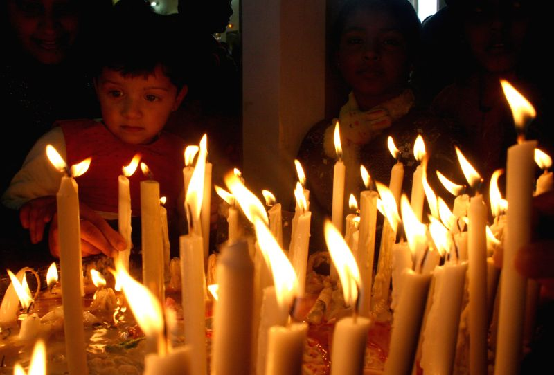 A child lights candles at Christ Church on Christmas in Shimla, on Dec 25, 2014.