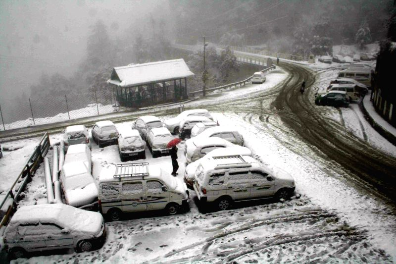 A man walks on a snow covered road of Shimla after the hill town received season's first snowfall on Dec 14, 2014.
