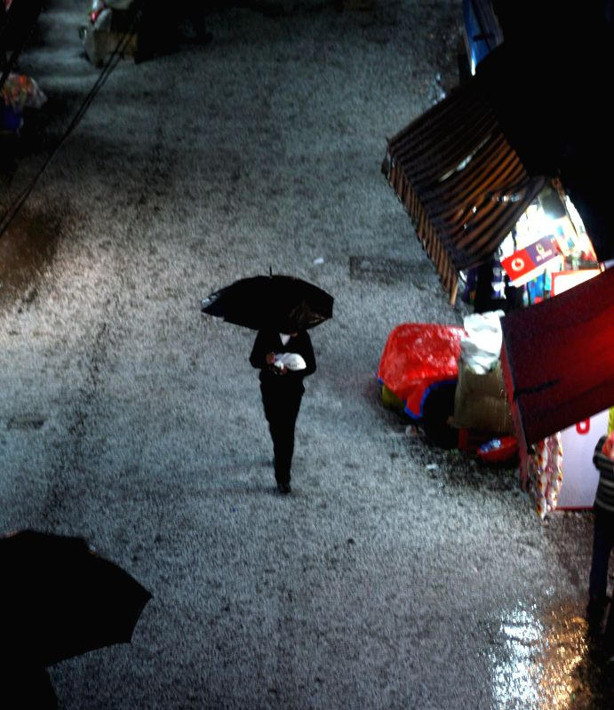 A man with an umbrella walks during a hail storm that hit Shimla on on Feb 18, 2015.
