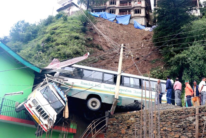Shimla: A road side parked HRTC bus and Bolero Camper hit by debris after massive landslide and pushed towards the road side building due to heavy rain near Mehli, in Shimla on Aug 18, 2019. (Photo: IANS)