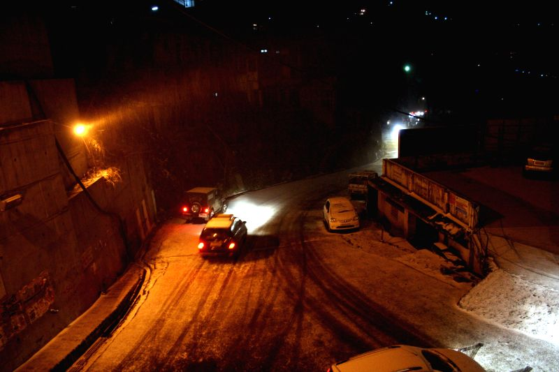 A vehicle move slowly during snowfall in Shimla on Jan. 29, 2015.