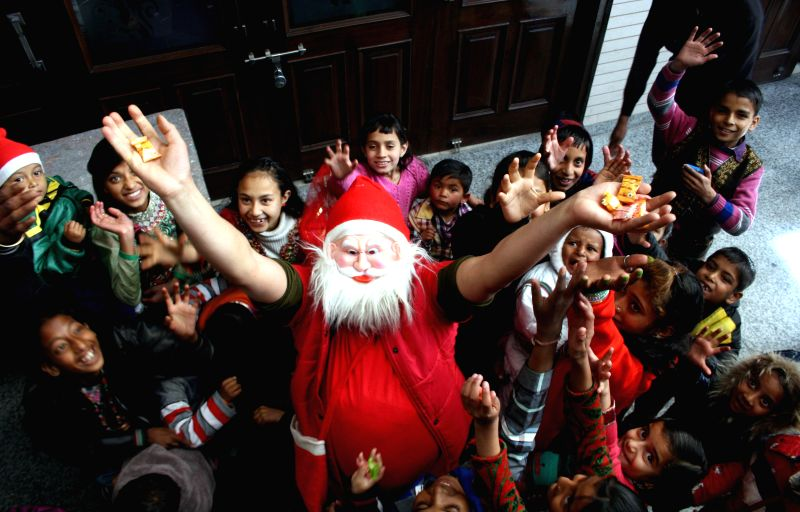 Children celebrate Christmas with Santa Claus in Shimla on Dec 21, 2014.