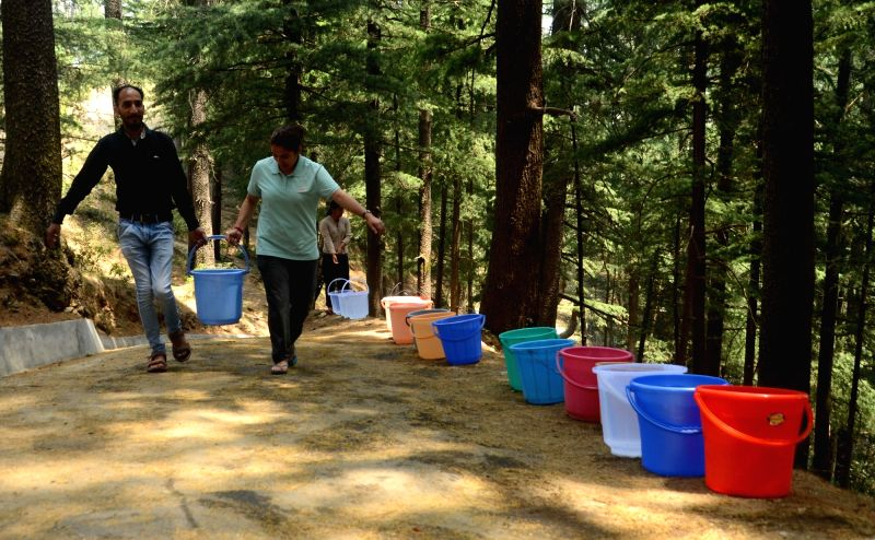 Shimla: People carry filled bucket after collecting water during water crisis that has hit many parts of the country during summers, in Shimla on May 30, 2018.