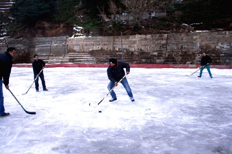People enjoy ice-hockey at ice skating rink in Shimla, on Dec 25, 2014.