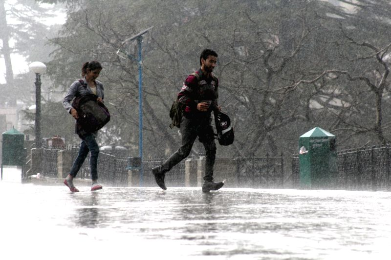 People run for shelter during rains in Shimla on March 29, 2015.