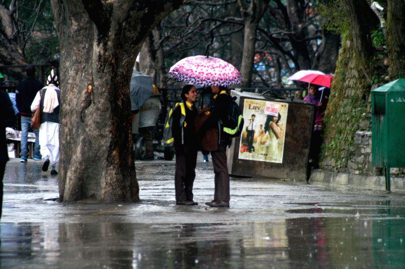 School students head towards school during rains in Shimla, on March 16, 2015.