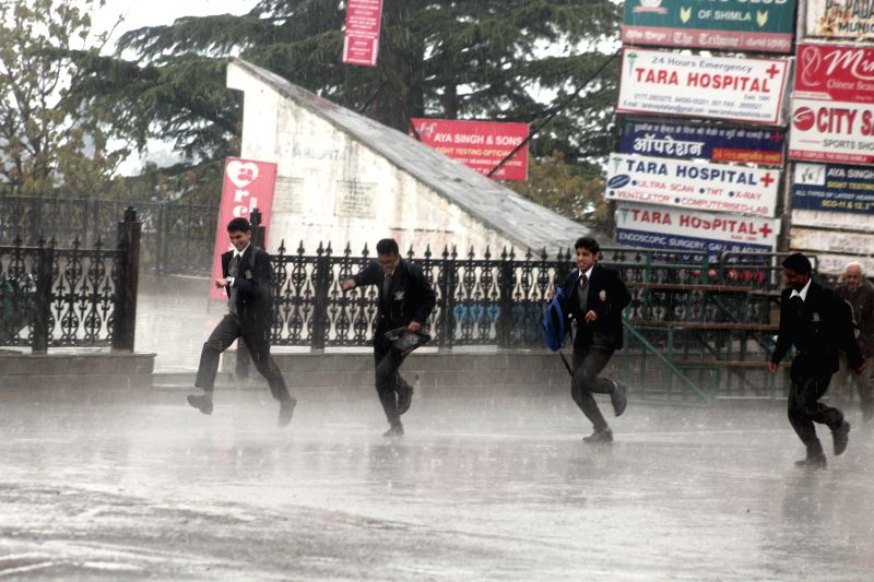 Students run for shelter as hailstorms hit Shimla on April 21, 2015.