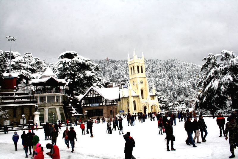 Tourists enjoy themselves at Ridge after season's first snowfall in Shimla on Dec 14, 2014.