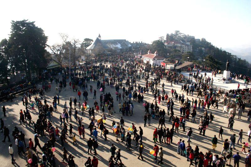 Tourists enjoy themselves on Christmas at Ridge in Shimla, on Dec 25, 2014.