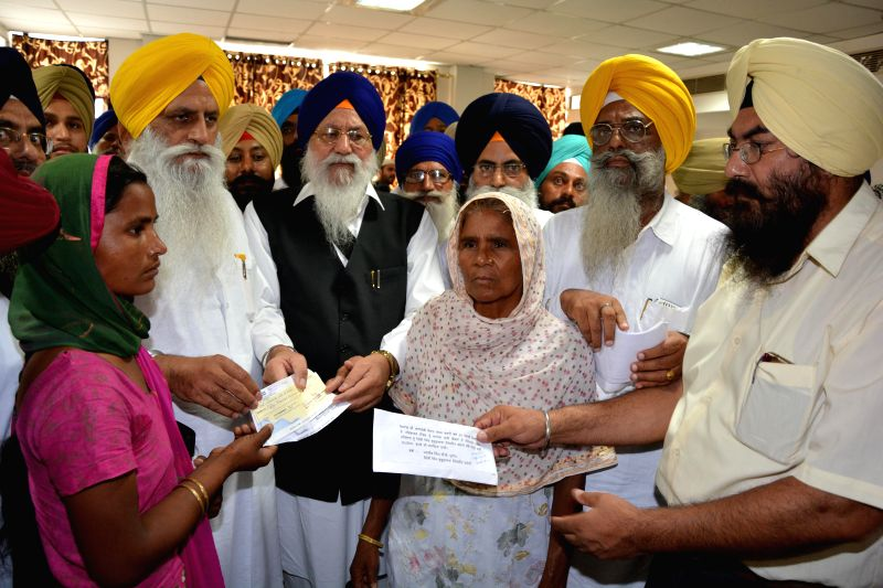 Shiromani Gurdwara Parbandhak Committee (SGPC) President Avtar Singh Makkar presents compensation cheques to family members of Indians abducted in Iraq during a function in Amritsar on July 1, 2014. - Avtar Singh Makkar
