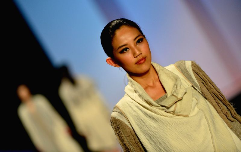 A model presents a creation during the 2014 Shishi International Fashion Week in Shishi, southeast China's Fujian Province, April 17, 2014.