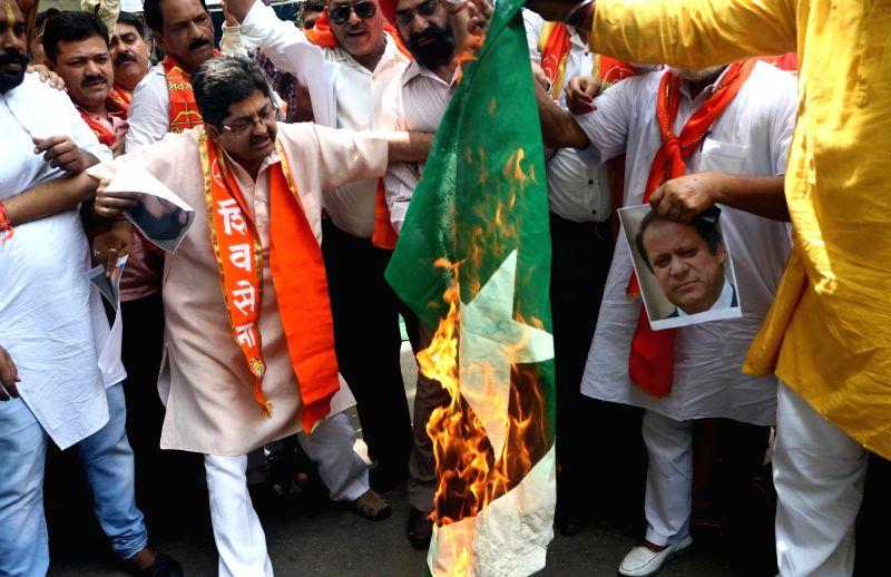 Shiv Sena activists burn Pakistan's national Flag and posters of Pakistan's Prime Minister Nawaz Sharif during a protest against Pakistan for terror attacked in India, in New Delhi on July ... - Nawaz Sharif
