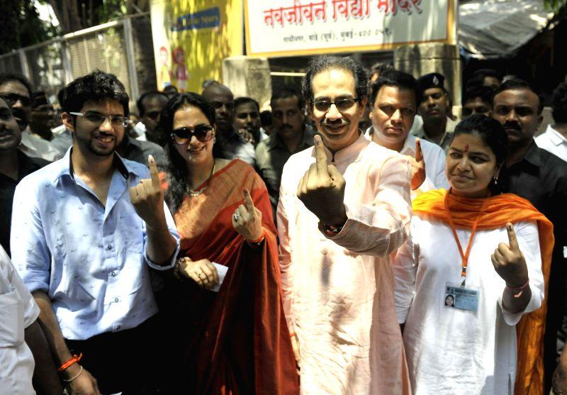 Shiv Sena president Uddhav Thackeray, Yuva Sena president Aditya Thackeray and BJP candidate for 2014 General Election from North Mumbai, Poonam Mahajan show their fore fingers marked with ...