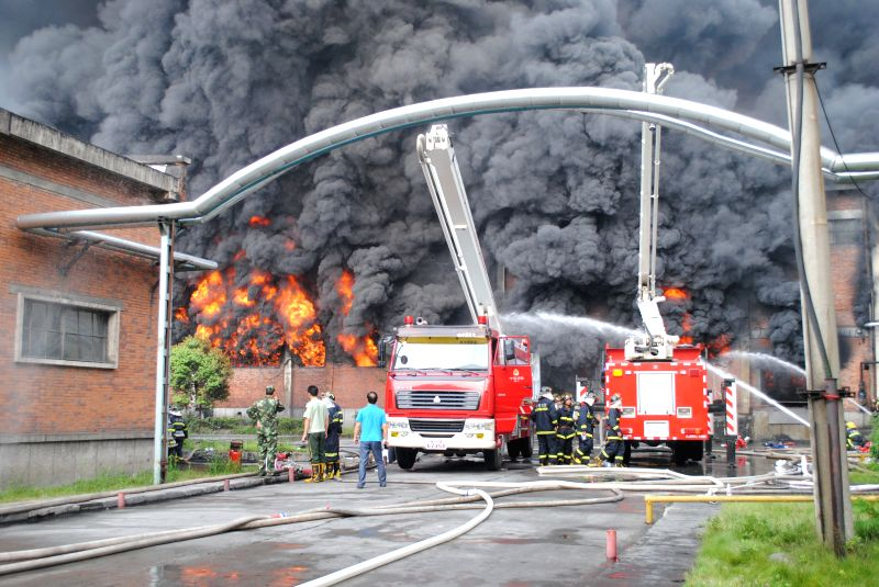 Fire fighters try to extinguish fire at a tyre warehouse of Dongfeng Tyre Factory in Shiyan, central China's Hubei Province, July 29, 2014. The fire occured at a ...