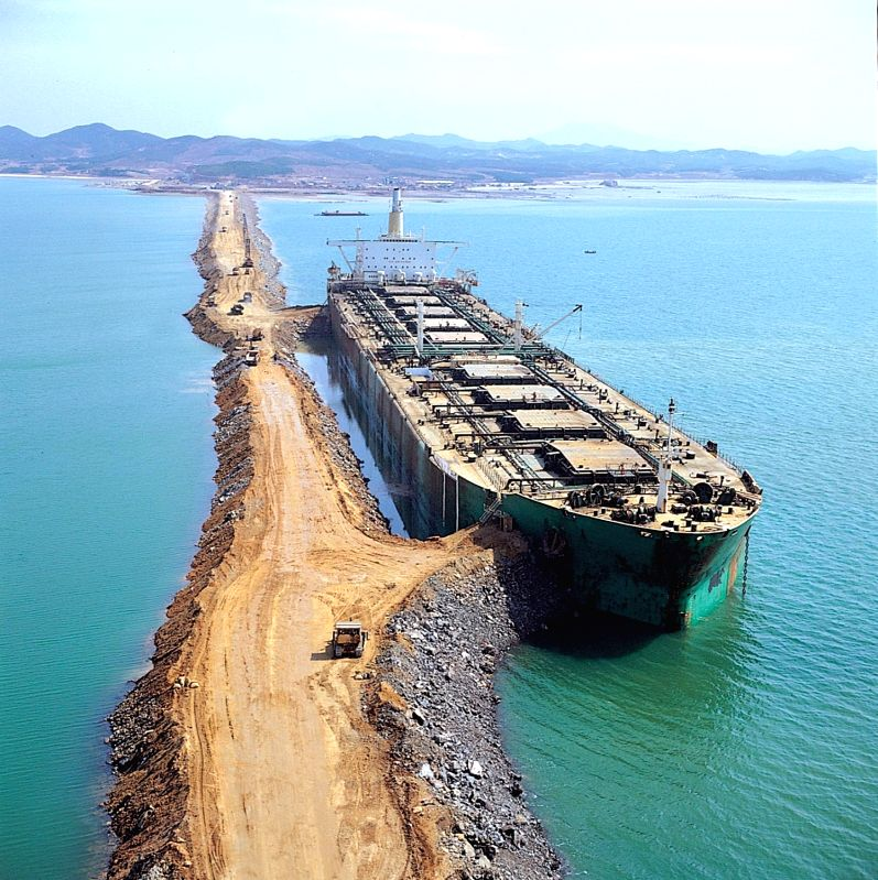 Shown is a photo of Hyundai Engineering & Construction undertaking a land reclamation project off Seosan, South Chungcheong Province, in 1980. A large oil tanker was used to stop the water flow ...