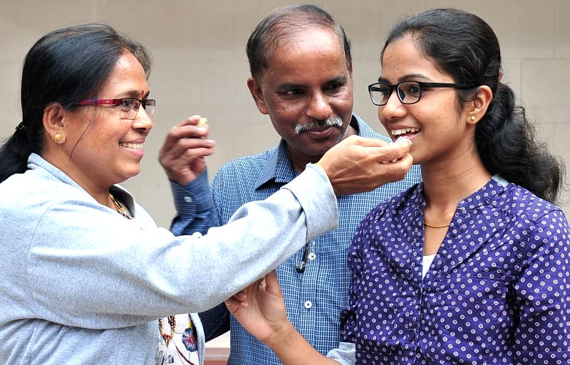 Shrinidhi PG, who has secured first rank (Commerce) in the Karnataka Second PUC exams celebrates with her family in Bengaluru on May 11, 2017.